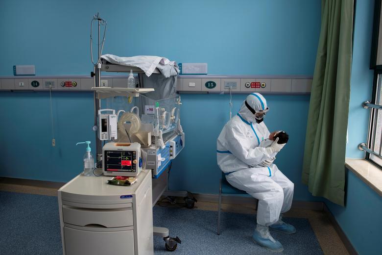 Медсестра в защитном костюме лечит ребенка с COVID-19, вызванным коронавирусом, в изоляторе детской больницы Ухань в Ухане, провинция Хубэй, Китай, 16 марта. China Daily via REUTERS
