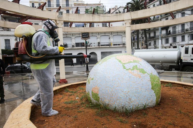 Працівник в захисному костюмі дезінфікує сквер у формі кулі, після спалаху коронавирусной хвороби, в Алжирі, Алжир, 23 березня. РЕЙТЕР / Рамзі Будіна