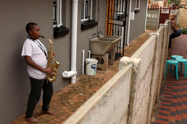 Ntsika Ntsele, 13 anos, toca saxofone alto enquanto seu vizinho olha por cima de uma cerca em Soweto, África do Sul, em 29 de março de 2020. REUTERS / Siphiwe Sibeko