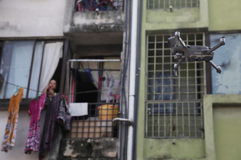 Женщина смотрит на беспилотник, который используется малазийской полицией, чтобы напомнить гражданам, чтобы они оставались дома во время распоряжения о контроле за передвижением из-за вспышки коронавирусной болезни (COVID-19) в Куала-Лумпуре, Малайзия, 24 марта 2020 года. REUTERS / Лим Хьюи Тен