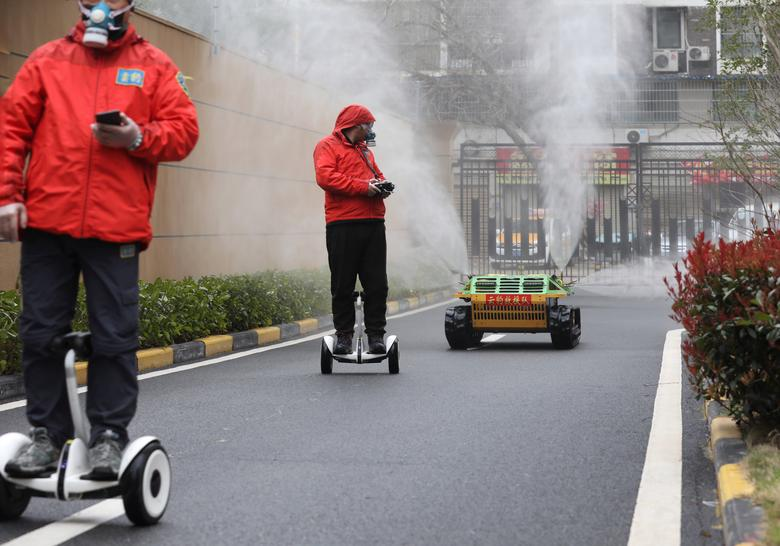 Рабочие ездят на умных самобалансирующихся самокатах, которые управляют автоматическим распылителем, распыляющим дезинфицирующее средство в жилом комплексе в Ухане, эпицентре новой вспышки коронавируса, провинция Хубэй, Китай, 3 марта 2020 года. China Daily via REUTERS