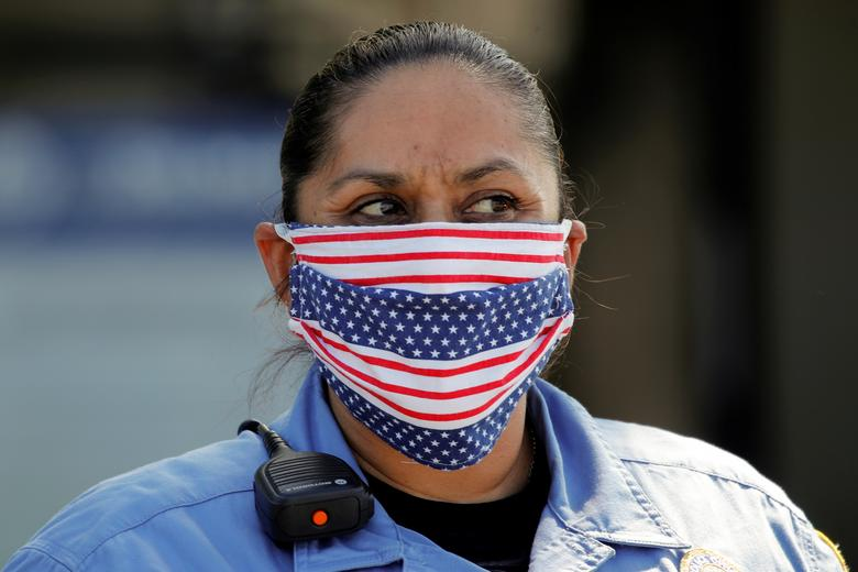 Поліцейський носить маску з американським прапором, допомагаючи Джейкобсу і Кушману в продовольчому банку Сан-Дієго нагодувати тисячі людей в продовольчому банку в Дель-Мар, Каліфорнія, 3 квітня 2020 року. РЕЙТЕР / Майк Блейк