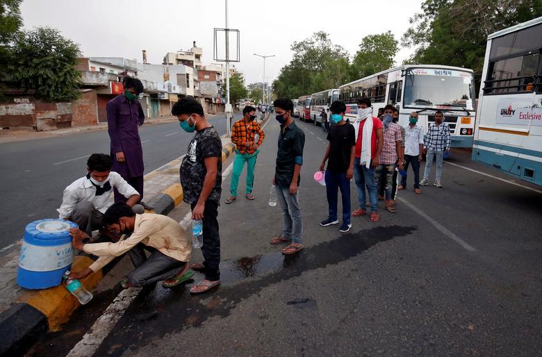 Рабочие-мигранты, которые оказались в западном штате Гуджарат из-за блокировки, наложенной правительством, наполняют бутылки питьевой водой, ожидая, когда они сядут на поезд, который доставит их в родной штат Бихар, в Ахмедабаде, Индия, май. 4. REUTERS / Амит Дейв