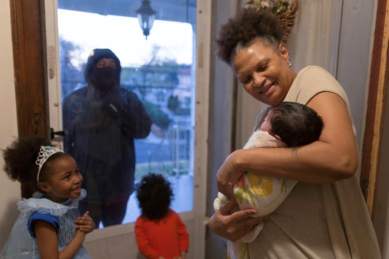 Хашим, важливий працівник в сфері охорони здоров'я, вперше бачить свою новонароджену племінницю, коли він вітає свою дочку і племінника через зачинені двері, оскільки він підтримує соціальну дистанцію зі своєю сім'єю, коли він працює під час спалаху в Нью-Рошелі, Нью-Йорк , 20 квітня 2020 року. REUTERS / Joy Malone