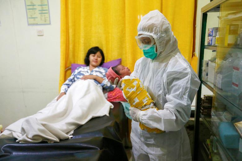 Медсестра в захисному костюмі тримає новонародженого в пологовому відділенні в Депок, недалеко від Джакарти, Індонезія, 13 квітня 2020 року. РЕЙТЕР / Аджен Динар Ульфіана