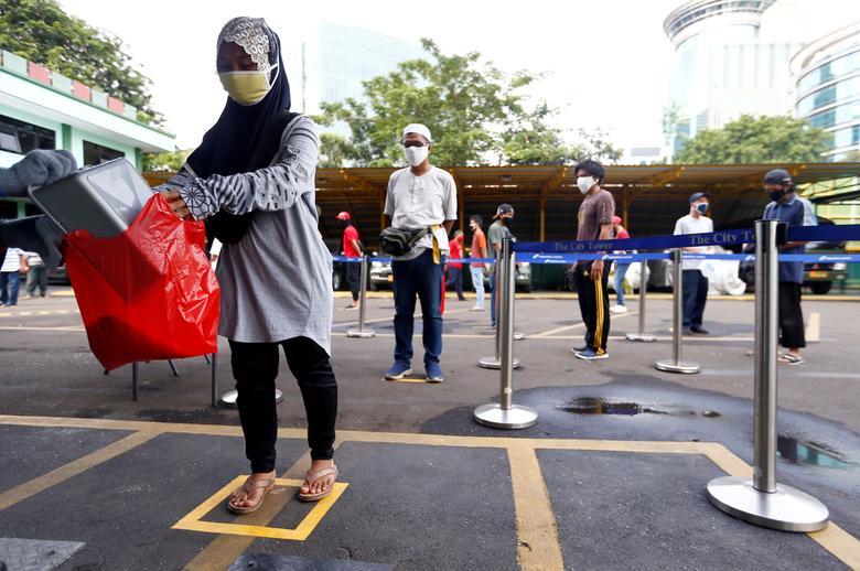Люди практикують соціальне дистанціювання, отримуючи рис від автоматичного банкомату з продажу рису в Джакарті, Індонезія, 4 травня. REUTERS / Ajeng Dinar Ulfiana