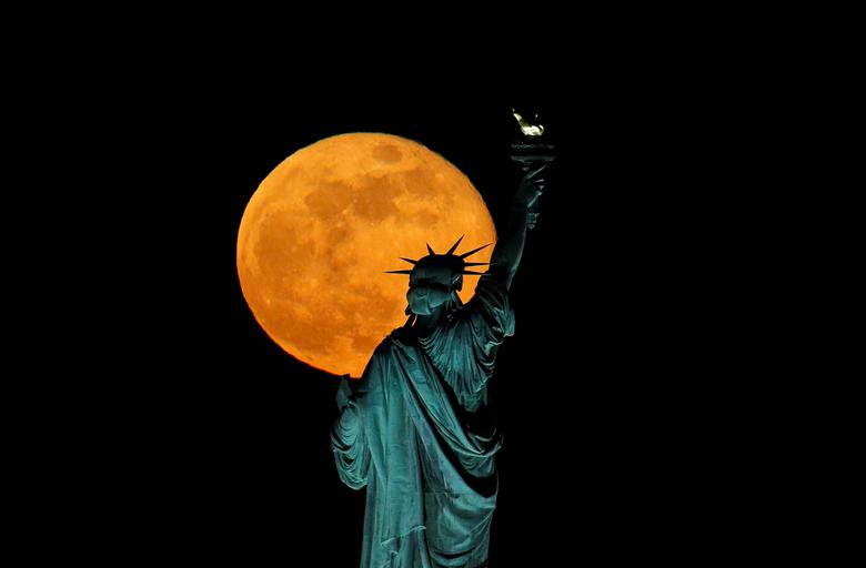 The full moon, also known as the Supermoon or Flower Moon, rises above the Statue of Liberty, as seen from Jersey City, New Jersey. REUTERS/Brendan McDermid
