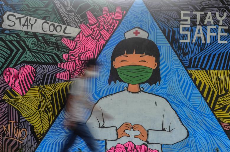 Человек идет около фрески, чтобы поддержать работников здравоохранения в Сиамисе, Западная Ява, Индонезия, 10 апреля. Antara Foto / Adeng Bustomi via REUTERS & nbsp;
