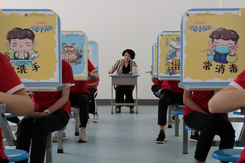Учитель ест вместе со студентами в школе, где ученики старших классов средней школы вернулись в кампус в Ичане, провинция Хубэй, Китай, 18 мая. China Daily via REUTERS & nbsp;