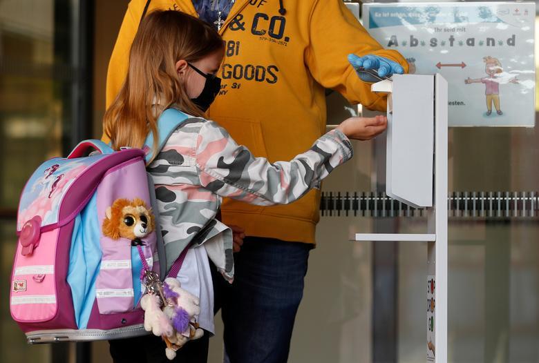 Ребенок в маске для лица дезинфицирует руки, когда прибывает в начальную школу в Брун-ам-Гебирге, Австрия, 18 мая. РЕЙТЕР / Леонард Фёгер