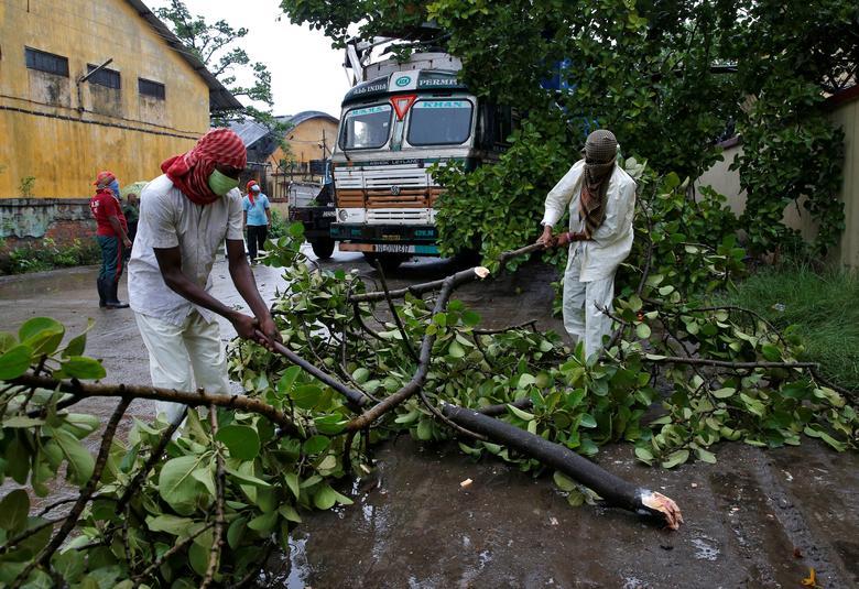Спасатели срезают ветки деревьев, которые упали на грузовик с прицепом после сильного ветра, вызванного циклоном Амфан, в Калькутте, Индия, 20 мая. РЕЙТЕР / Рупак Де Чоудхури