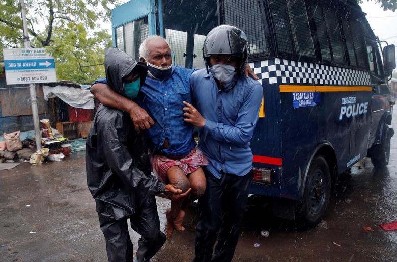 Полицейские доставляют инвалида в более безопасное место после его эвакуации из района трущоб перед тем, как Циклон Амфан выйдет на берег, в Калькутте, Индия, 20 мая. РЕЙТЕР / Рупак Де Чоудхури