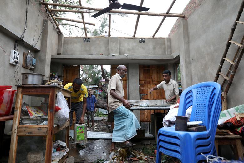 Мужчины спасают предметы из поврежденного магазина после того, как Циклон Амфан совершил посадку на берег, в районе Южные 24 Парганаса в восточном штате Западная Бенгалия, Индия, 21 мая. РЕЙТЕР / Рупак Де Чоудхури