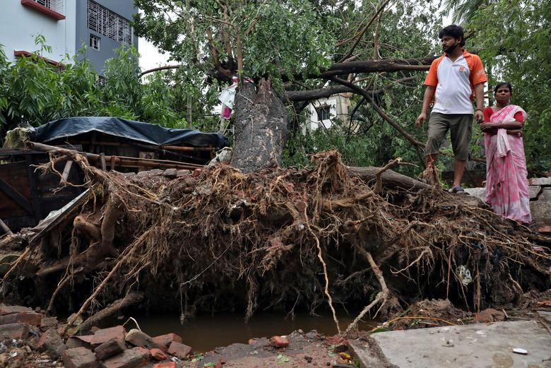 Люди стоят рядом с вырванным с корнем деревом после того, как Циклон Амфан высадился на берег в Калькутте, Индия, 21 мая. РЕЙТЕР / Рупак Де Чоудхури