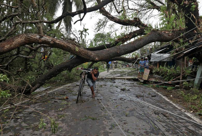 Человек идет со своим велосипедом под вырванным с корнем деревом после того, как Циклон Амфан обрушился на сушу в районе Южная 24 Парганас, в восточном штате Западная Бенгалия, Индия, 21 мая. РЕЙТЕР / Рупак Де Чоудхури