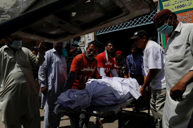 Rescue workers and relatives move a body of a victim, who was killed in a plane crash, outside a morgue in Karachi, Pakistan May 23, 2020. REUTERS/Akhtar Soomro