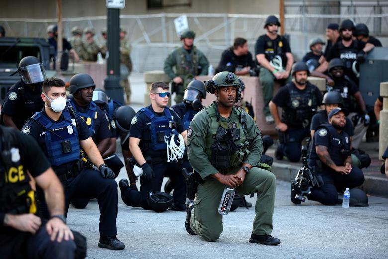 Memurlar, 1 Haziran Atlanta şehir merkezindeki bir protesto sırasında protestocularla diz çöktü. REUTERS / Dustin Chambers