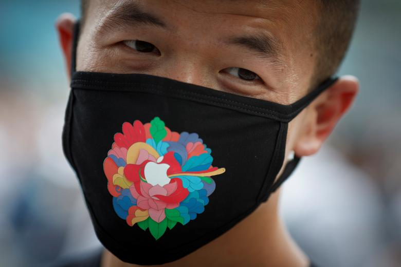 A man wears an Apple-branded face mask as he waits for the opening of the new Apple flagship store in Sanlitun in Beijing, China, July 17, <span dir=
