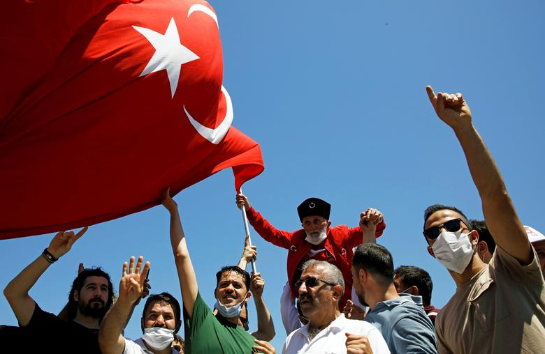 People gesture as they wait for the beginning of Friday prayers outside Hagia Sophia Grand Mosque, July <span dir=