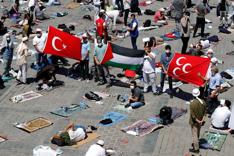 People hold Turkish and Palestinian flags as they wait for the beginning of Friday prayers outside Hagia Sophia Grand Mosque, July <span dir=
