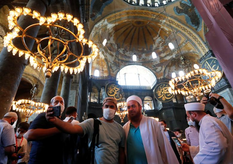 People take a selfie as they visit Hagia Sophia Grand Mosque after Friday prayers, July <span dir=