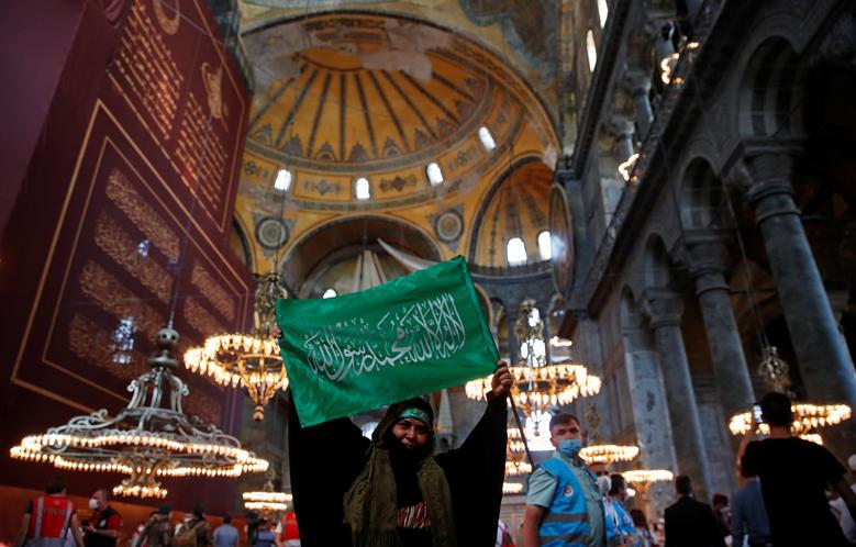 A woman holds a flag as she attends afternoon prayers and visits Hagia Sophia Grand Mosque, July <span dir=