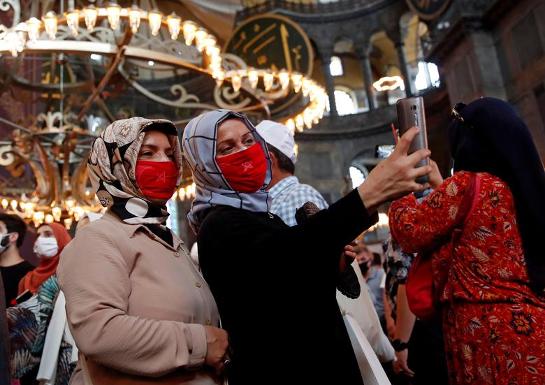 Women take a selfie as they attend afternoon prayers and visit Hagia Sophia Grand Mosque, July <span dir=
