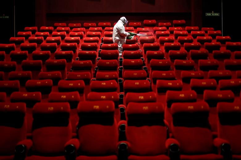 A worker wearing protective gear sprays disinfectant inside an empty PVR multiplex that was closed in New Delhi, India July 31, 2020. REUTERS/Adnan Abidi