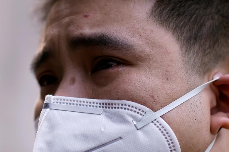 A man wearing a face mask cries in Wuhan, Hubei province, as China holds a national mourning for those who died of the coronavirus, April 4. REUTERS/Aly Song