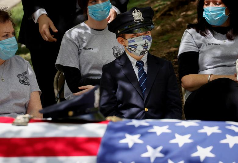 Gavin Roberts wears his father's police hat as he looks at the flag-draped casket of his father, Glen Ridge Police Department officer Charles Roberts, after the 45-year-old father of three died of the coronavirus in Glen Ridge, New Jersey, May 14. REUTERS/Mike Segar
