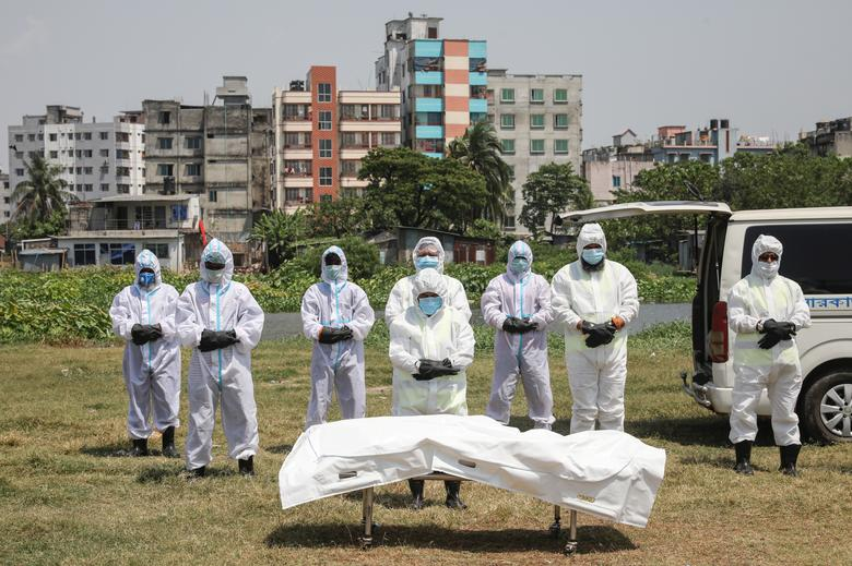 People offer funeral prayers for a man who died due to the coronavirus before his burial at a graveyard in Dhaka, Bangladesh, April 6. REUTERS/Mohammad Ponir Hossain