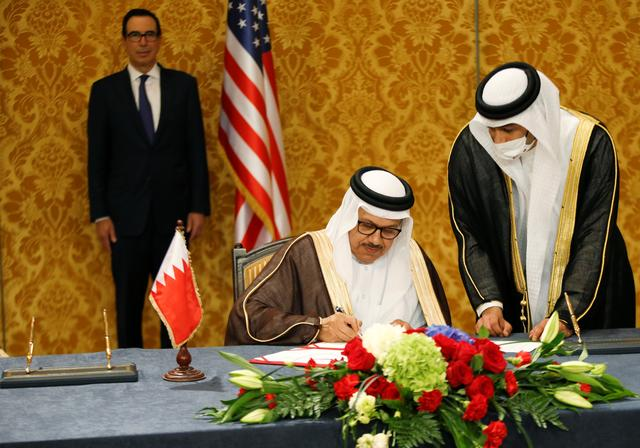 A Bahraini official signs an agreement with an Israeli delegation led by Israeli National Security Advisor Meir Ben Shabbat in Manama, Bahrain, October 18, 2020. REUTERS/Ronen Zvulun/Pool