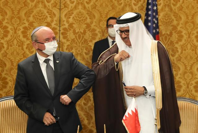An Israeli delegation led by Israeli National Security Advisor Meir Ben Shabbat and Bahraini official bump elbows after signing an agreement in Manama, Bahrain, October 18, 2020. REUTERS/Ronen Zvulun/Pool