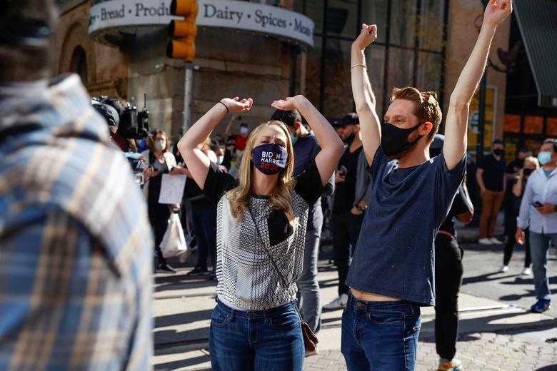 People react as media announce that Joe Biden has won the 2020 U.S. presidential election, in, Philadelphia, November 7. REUTERS/Rachel Wisniewski