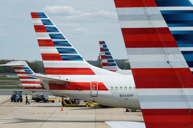 A member of a ground crew walks past American Airlines planes parked at the gate during the coronavirus disease (COVID-19) outbreak at Ronald Reagan National Airport in Washington, U.S., April 5, 2020. REUTERS/Joshua Roberts