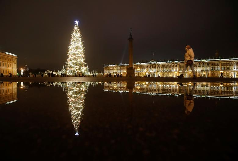 A woman walks near a Christmas tree for the upcoming holiday season in Palace Square in central Saint Petersburg, Russia, December 22, 2020. REUTERS/Anton Vaganov