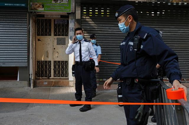 Police are seen outside the office of Daniel Wong Kwok-tung, a lawyer who tried to help the 12 people detained in mainland China, in Hong Kong, China January 14, 2021. REUTERS/Tyrone Siu