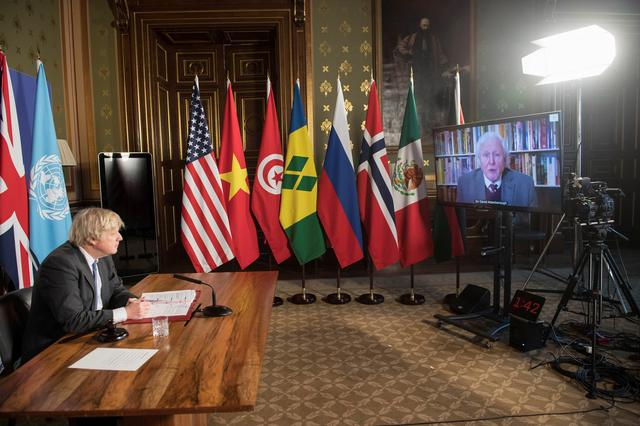 Prime Minister Boris Johnson watches a video address by Sir David Attenborough at a session of the UN Security Council on climate and security at the Foreign, Commonwealth and Development Office in London, Britain February 23, 2021. Stefan Rousseau/Pool via REUTERS