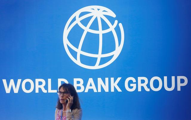 FILE PHOTO: A participant stands near a logo of World Bank at the International Monetary Fund - World Bank Annual Meeting 2018 in Nusa Dua, Bali, Indonesia, October 12, 2018. REUTERS/Johannes P. Christo