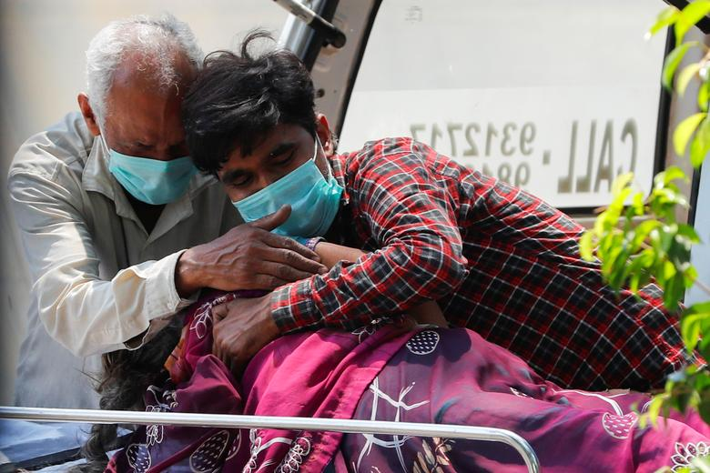 Relatives mourn over the body of a woman who died from the coronavirus outside Lok Nayak Jai Prakash Narayan Hospital, one of India's largest facilities for treating COVID-19 patients only, in New Delhi, April 22. REUTERS/Adnan Abidi