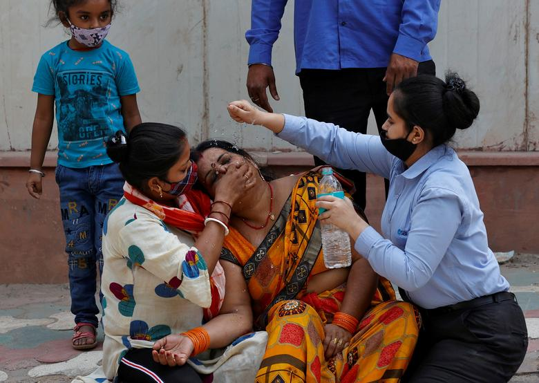 A woman is consoled after her husband died due to the coronavirus outside a mortuary of a COVID-19 hospital in New Delhi, India, April 15. REUTERS/Danish Siddiqui