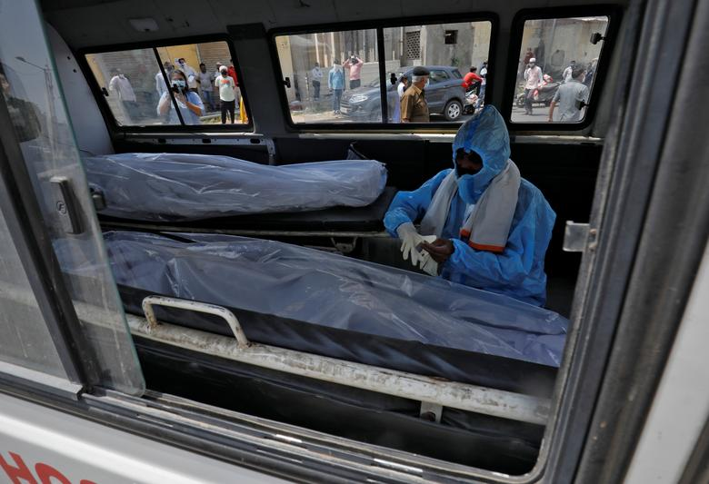A man wearing a protective suit sits next to the bodies of coronavirus victims inside an ambulance at a mortuary of a COVID-19 hospital in Ahmedabad, April 15. REUTERS/Amit Dave