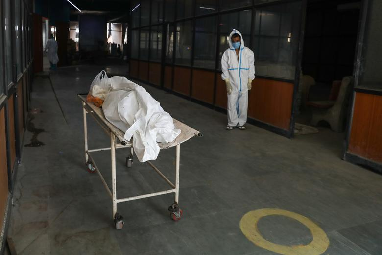 A man waits next to the body of his mother, who died from the coronavirus, at a crematorium in New Delhi, April 9. REUTERS/Anushree Fadnavis