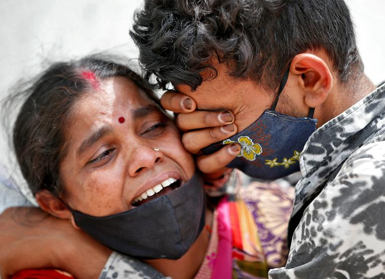 A woman mourns with her son after her husband died due to the coronavirus outside a mortuary of a COVID-19 hospital in Ahmedabad, April 20. REUTERS/Amit Dave