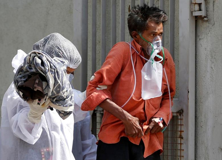 A patient with breathing problems is helped to walk towards an ambulance as he is moved to a hospital in Ahmedabad, April 14. REUTERS/Amit Dave