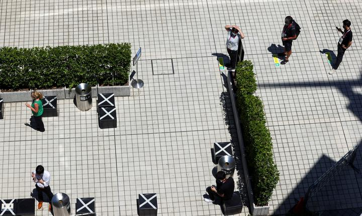 FILE PHOTO: Smokers wait their turn in a queue in Tokyo