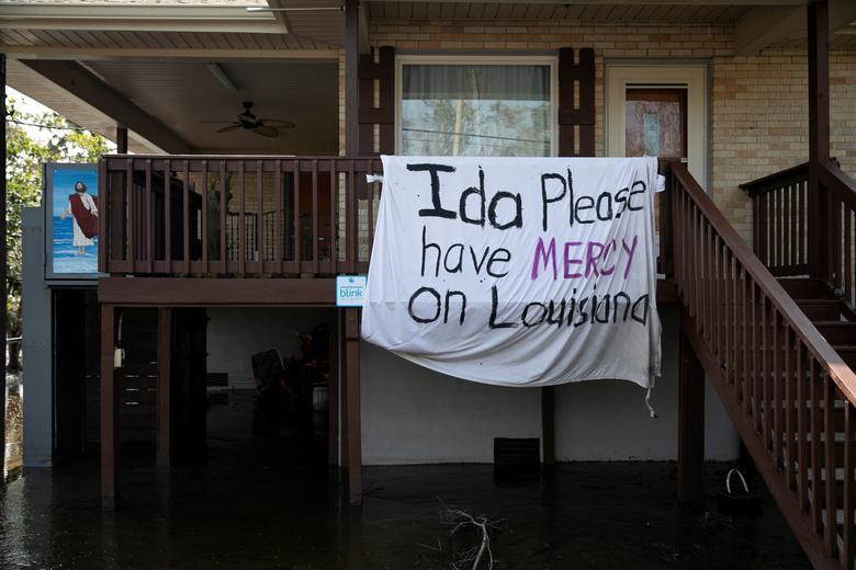 "A blanket that reads ""Ida please have mercy on Louisiana"" hangs outside a house, following Hurricane Ida landfall in Louisiana, in Jean Lafitte, Louisiana. REUTERS/Marco Bello"