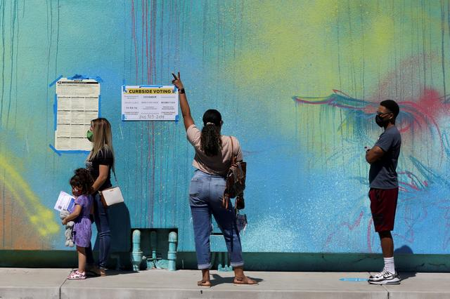 A woman gestures as people wait to vote in the California gubernatorial recall election outside the Museum of Latin American Art (MOLAA) in Long Beach, California, U.S., September 14, 2021. REUTERS/David Swanson
