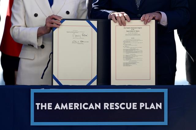 FILE PHOTO: House Speaker Nancy Pelosi (D-CA) and Senate Majority Leader Chuck Schumer display the ''American Rescue Plan'' during the enrolment ceremony following passage of U.S. President Joe Biden's $1.9 trillion coronavirus disease (COVID-19) relief bill on Capitol Hill in Washington, U.S., March 10, 2021. REUTERS/Erin Scott