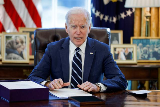 FILE PHOTO: U.S. President Joe Biden signs the American Rescue Plan, a package of economic relief measures to respond to the impact of the coronavirus disease (COVID-19) pandemic, inside the Oval Office at the White House in Washington, U.S., March 11, 2021. REUTERS/Tom Brenner